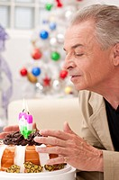 Domestic Life, a senior man blowing the candle on the cake