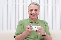 Domestic Life, a senior man playing video game and smiling happily
