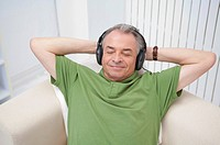 Domestic Life, a senior man lying on sofa and listening music with eyes closed