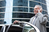 Senior businessman holding the door of car and using mobile phone with smile