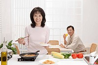 Couple, Wife cooking food and husband drinking near the table with smile
