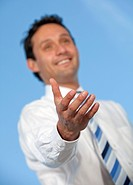 Business man stretching his hand isolated over blue