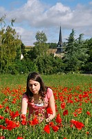 YOUNG GIRL WITH POPPIES, GATHERING FLOWERS IN FRONT OF THE CHURCH IN THE VILLAGE OF ROUVRES, EURE_ET_LOIR 28, FRANCE