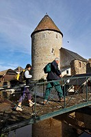 WALKERS ON A HIKE ON A FOOTBRIDGE IN FRONT OF THE KING´S TOWER, AN OLD 13TH CENTURY KEEP PROTECTED BY THE DITCHES THAT SURROUND THE TOWN, BONNEVAL, EU...