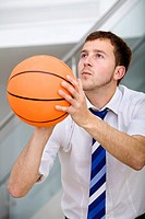 Handsome business man ready to throw a basketball