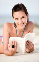 beach woman reading a book lying on the sand