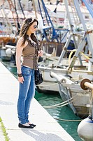 Attractive young woman and fishing boats