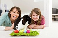 Mother and daughter with Easter Eggs and rabbit.