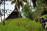 Backs of adults and children right frame hiking up grassy hill to visible saddleback roofline of haus tambaran spirit house with small local boy waist...