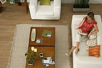 Woman relaxing on sofa with book on lap, talking on cell phone