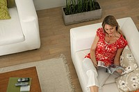 Woman relaxing in living room reading magazine (thumbnail)