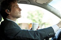 Businessman driving to work with cup of coffee in hand