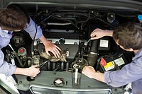 Mechanics reparing car engine