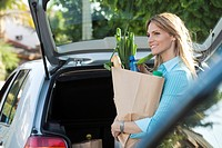 Woman putting groceries in back of hatchback