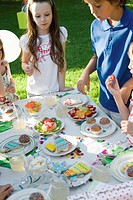 Children around sweets table at outdoor birthday party