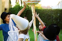 Children reaching to pull streamers attached to pull string pinata