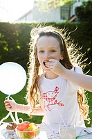 Girl holding balloon and eating candy