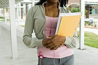 Student listening to MP3 player, carrying notebook, cropped
