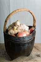 Basket containing onions, garlic, and ginger root