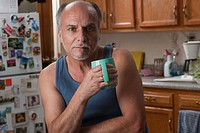 Serious Caucasian man drinking coffee in kitchen