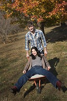 Caucasian man pushing wife in wheelbarrow