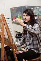 Hispanic student painting in art class