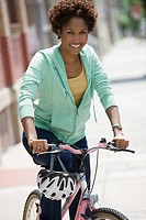 Black woman on bicycle in city