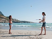 Mother and daughter playing paddleball on beach