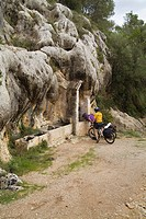 BARRANC DE BINIGAUS MENORCA Two touring cyclists looking at traditional Menorcan limestone cliff well