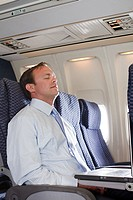 Businessman sleeping in an airplane