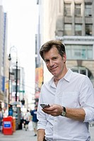 Portrait of mature man in street with smartphone