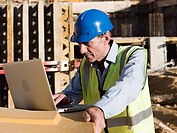 Mature man using laptop on construction site