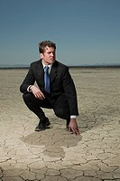 Businessman crouching in desert landscape