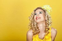 Young blonde woman against yellow background