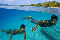 Over under image of marshallese boys swimming underwater, Majikin Island, Namu Atoll, Pacific, Marshall Islands
