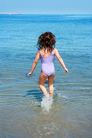 brunette little girl running into beach water back view summer vacation