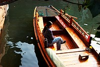 Woman sitting on a boat, Zhouzhuang, Jiangsu Province, China
