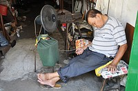 Malacca (Malaysia): a man sleeping in his antique shop, in front of a fan, in Chinatown