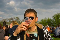 Russian man in his 30s drinking beer out of plastic cup Zizkov district Prague Czech Republic Europe