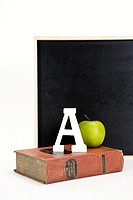 apple, A and dictionary in front of blackboard