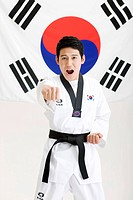 man in Taekwondo uniform in front of Korean flag, Taegeukgi