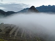 Early morning mist over the ancient Inca ruins at Machu Picchu near Cusco in Peru