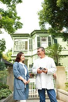 Husband and wife standing in front of a house