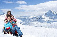 Portrait of happy family hugging on snowy mountain