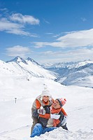 Portrait of happy couple hugging on snowy mountain