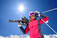 Portrait of smiling woman holding skis and ski poles under sun in blue sky