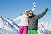 Young couple in ski wear, smiling at camera