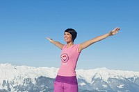 Young smiling woman with arms raised, mountains in background