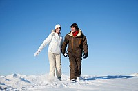 Young couple holding hands, walking in snow