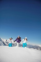 Three teenage girls in ski clothes, running in snow